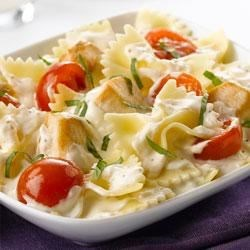 Creamy Chicken-Bruschetta Pasta Recipe - Topped with fresh basil and ready to serve in less than 30 minutes, this one-dish dinner features chunks of browned chicken and grape tomatoes simmered in a creamy garlic sauce with farfalle pasta.