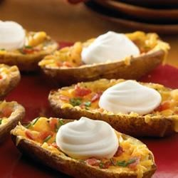 Daisy Brand Potato Skins Recipe - Make your own baked potato skins--these are buttery, cheesy, filled with bacon, and topped with a dollop of Daisy and a sprinkle of chives!