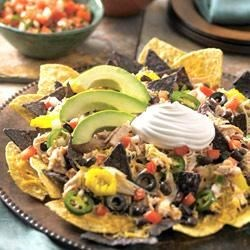 Daisy Brand Chicken Nachos Recipe - Shredded chicken in a creamy blend of sour cream, salsa, and spices is baked on a bed of blue corn tortillas with black beans, peppers, and olives--what a snack!