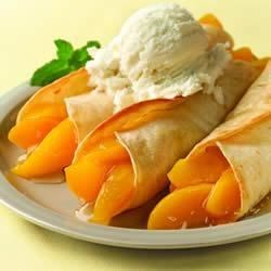 Peachy Enchiladas Recipe - Peach filling and a sweet almond syrup make these tasty dessert enchiladas impossible to pass up. Serve warm with vanilla ice cream.