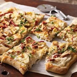 Grilled Chicken Flatbread Recipe - Pizza dough is spread with a creamy, garlic sauce then topped with grilled chicken breast slices, roasted red peppers, artichoke hearts, and cheese for an easy lunch or light supper.