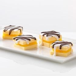 Quick Cake Bites Recipe - Pound-cake squares filled with a creamy, lemon filling and drizzled with white frosting make delicious, bite-size sandwich treats!