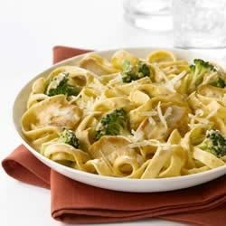 Creamy Pomodoro Pasta Recipe - Strips of browned chicken and broccoli florets are served over fettucine with a creamy tomato basil sauce, and then topped with grated Parmesan cheese.