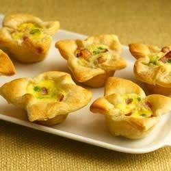Onion-Cheese Custard Tartlets Recipe - Crescent dough in mini muffin cups forms a flaky crust that holds a creamy appetizer filling.