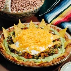 Dannon 7-Layer Dip Recipe - This favorite layered dip with browned ground beef, refried beans and shredded cheese gets a fresh update with a layer of creamy yogurt.