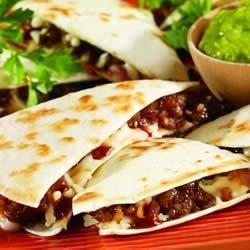 BBQ Quesadilla Recipe - These zesty quesadillas are filled with hot sausage, spicy barbecue sauce and cheese. Served with sour cream and salsa, they're great for lunch or as appetizers.