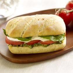Tomato Basil Mozzarella Melt Recipe - Mini baguettes spread with pesto are filled with tomato and mozzarella slices, then heated until warm and cheese is melted.