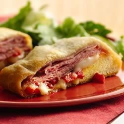 Easy Crescent Muffuletta Recipe - Make a quick and easy version of this New Orleans classic sandwich layered with salami, roasted red peppers and provolone, wrapped in a flaky Crescent crust.