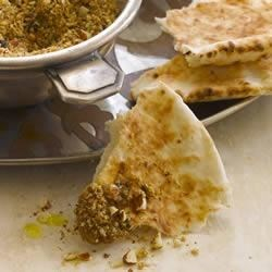 Almond Dukkah Recipe - A spicy, crumbly seasoning mix made from sesame seeds, coriander, cumin, and almonds makes a tasty flavoring for pita bread. Dip the bread in olive oil, then into the almond dukkah to serve.