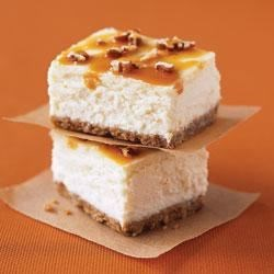 Double Caramel-Pecan Cheesecake Bars Recipe - A dreamy cheesecake with caramel on a pecan crust is topped with more chopped pecans and drizzled with caramel.