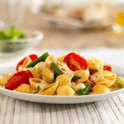 Mini Shells with Grape Tomatoes, Green Beans, and Mozzarella Recipe - Fresh green beans and grape tomatoes are tossed with Barilla White Fiber pasta shells and topped with marinated mozzarella pieces.
