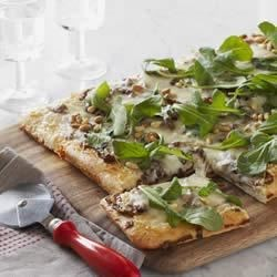 Caramelized Onion and Arugula Pizza Recipe - Create your own gourmet pizza topped with caramelized onions, fresh rosemary, arugula, and pine nuts on a cheesy, homemade crust.