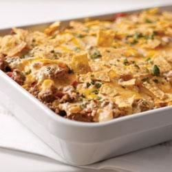 Tex-Mex Beef and Rice Casserole Recipe - A cheesy rice mixture is topped with creamy ground beef, tomatoes, Mexican-style corn, and more cheese and baked until piping hot.