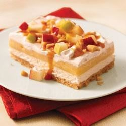 Caramel Apple Dessert Recipe - Two creamy layers on a crumb crust are topped with chopped red and green apples and peanuts.