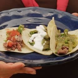 Angelica's Carne Asada Tacos Recipe - Mexican night starts with carne asada--tender citrus-marinated beef piled high on corn tortillas with grilled cactus, cilantro, and 2 types of zesty salsa.