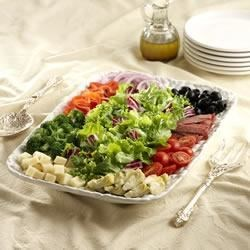 Antipasto Salad Platter Recipe - This crisp, fresh salad contains all your favorite antipasto ingredients--artichoke hearts, mozzarella cheese cubs, sweet little tomatoes, salami, and red bell pepper strips.
