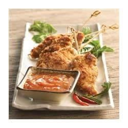 Coconut Chicken with Apricot Ginger Dipping Sauce Recipe - Coated in a peanut sauce, dipped into coconut/panko breading, and cooked until golden brown, these crispy chicken tenders are served with an apricot-ginger dipping sauce.