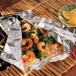 Shrimp and Broccoli Packets Recipe - Shrimp, broccoli, and rice cook together with garlic and seasonings in foil packets for a flavorful, fuss-free dinner.
