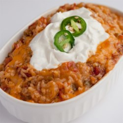 Easy Authentic Spanish Rice Recipe - White rice simmers in Mexican-style tomatoes, onions, and jalapeno peppers for a quick and easy side dish. Top with shredded Cheddar and sour cream, if desired.
