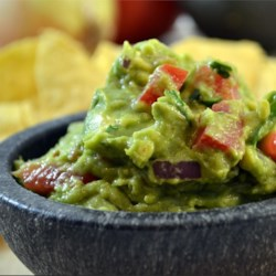 Fall in Love (with) Guacamole Recipe - This guacamole will make anyone fall in love with avocados. A smooth dip made with avocados, lime juice, roma tomatoes, and cilantro is perfect for any occasion!