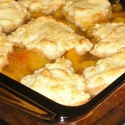 Fresh Peach Cobbler I Recipe - Sweet fresh peaches are cooked on the stovetop to make a thick and juicy fruit filling, topped with a homemade biscuit mixture, and baked until golden brown. Serve warm with whipped cream, whipped topping, or ice cream.