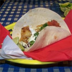 Fort Worth Fish Tacos Recipe - Fish fillets (tilapia, cod, or crappie) are coated in a spiced beer batter, fried, and served in warm flour tortillas with shredded cabbage, salsa, and a cilantro cream sauce.