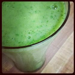 Kale Orange Banana Smoothie Recipe - A fresh orange, a pair of ripe bananas, and a kale leaf are blended into a pudding-like smoothie for a wholesome breakfast drink.