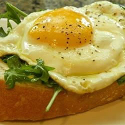 Open Faced Egg Sandwiches with Arugula Salad Recipe - Crusty slices of rustic bread spread with garlicky mayonnaise make a great foundation for open-faced sandwiches topped with lightly dressed arugula and a fried egg. It's a great quick lunch.