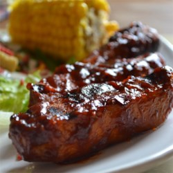 Simple BBQ Ribs Recipe and Video - Simply seasoned ribs are boiled, then oven baked in the barbeque sauce of your choice for easy BBQ ribs.