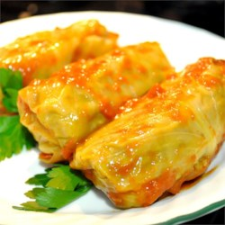 Stuffed Cabbage Rolls Recipe - Cabbage leaves filled with ground beef and rice are simmered in tomato soup for this Polish-inspired favorite.
