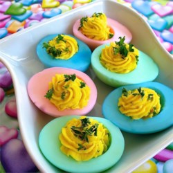 Easter Deviled Eggs Recipe - Your guests, whether they're grown-ups or kids, will love these pretty pastel-colored deviled eggs. Use any desired food coloring to tint the egg whites before filling. Make a few plain ones to add variety to your platter.