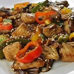 Sesame Chicken Recipe - An authentic rendition of a sublime Asian dish.  Chicken first steeps in soy, lemon, ginger and rice wine marinade, then is stir-fried with mushrooms and green pepper in sesame oil.  Toasted sesame seeds add the final touch.