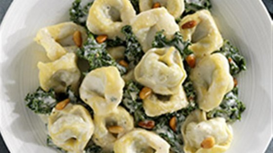 Ricotta and Spinach Tortelloni with Creamy Parmigiano Sauce, Kale and Pine Nuts
