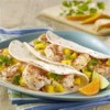 Spicy Shrimp Tacos Recipe - Spicy sauteed shrimp are served in soft tacos with chopped mango, red onion, and a drizzle of kicked-up Ranch dressing.
