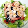 Greek-Style Shrimp Salad on a Bed of Baby Spinach Recipe - Grilled shrimp and Greek flavorings (tomato, feta, Kalamata olives, oregano) commingle in this salad.