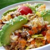 Spicy Dorito(R) Taco Salad Recipe and Video - A slightly spicy taco salad combines lettuce with ground seasoned beef, cheese, beans, and tortilla chips, all tossed with a tangy homemade dressing.