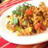 Southwestern Pasta Salad Recipe - Pasta is tossed with a zesty dressing of lime juice, chili powder and cumin. Corn, black beans, red and green bell pepper, tomatoes and cilantro add texture, flavor and color.