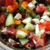 Greek Salad III Recipe - A classic. Tomatoes, olives, feta, peppers, onions and cucumbers, all sliced, chopped and waiting to be tossed with a great dressing. This  recipe has one - red wine vinegar, olive oil, lemon juice and herbs. Toss and enjoy.