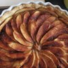 French Apple Tart (Tarte de Pommes a la Normande) Recipe - This is a marvelous apple tart that can be made in a pie plate or tart pan if you have one. A frangipane filling really brings together the flavors of fall, and the apples create a beautiful design.