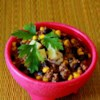 Southwestern Black Bean Stew Recipe - Browned ground beef seasoned with a package of taco seasoning mix is combined with whole kernel corn and canned black beans in this stew served with a dollop of sour cream and grated cheddar cheese.