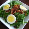 Wilted Spinach Salad Recipe - This rich and flavorful salad features fresh spinach and green onions drizzled with a warm, sweet, vinegary dressing, and sprinkled with crunchy bacon and tender bits of hard boiled egg.