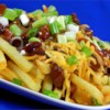 Chili Cheese Fries Recipe - Smothered in chili and cheddar cheese sauce, these easy chili cheese fries are a complete meal in themselves.