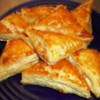 Feta Cheese Foldovers Recipe - Golden puffed pastries are filled with a feta cheese mixture. These can be made ahead, and popped into the oven after your guests arrive.