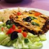 Layered Chicken and Black Bean Enchilada Casserole Recipe - Layers of sauce and tortillas mingle with a seasoned chicken and black bean mixture. This is a delicious and easy recipe best served with a side of Spanish rice. You may wish to substitute low fat sour cream.