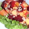 Beet, Orange and Apple Salad Recipe -  What a nice, colorful salad. Thick wedges of cooked beets, thinly sliced apples and orange sections are dressed with a delicious vinaigrette and spooned onto a bed of shredded beet greens.