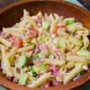 Greek Pasta Salad Recipe - Penne pasta has great company in this robust salad that is hearty enough to serve as an entree. Tomatoes, cucumbers, green peppers, sweet onion and black olives are tossed with the pasta and an herbed oil and lemon juice dressing.