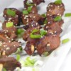 Hoisin-Ginger Beef Skewers Recipe - An Asian-style marinade made with hoisin sauce, fresh ginger and garlic, sesame oil, and lime juice adds zest to these flank steak skewers.