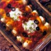 Chicken and Cheese Enchiladas Recipe - Chunks of chicken, diced green chiles and a cheesy sauce-with-a-kick are rolled up in tortillas, covered with more sauce and baked to perfection.