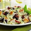 Mediterranean Chicken Orzo Recipe - A taste of the Mediterranean is only minutes away with this simple orzo and chicken pasta tossed with tomatoes, olives, basil, lemon juice, and grated Parmesan cheese.