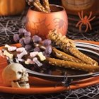 Spook-tacular Chocolate-Dipped Pretzels - Dipped in melted chocolate morsels and decorated with a variety of spookalicious candies, these festive treats are a frightfully fun way to celebrate the haunting night ahead.